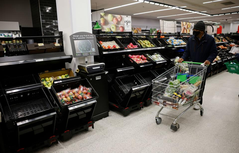 A shopper wearing a face mask or covering due to the COVID-19 pandemic, pushes a trolley past empty fruit and vegetable troughs inside an ASDA supermarket in Walthamstow in north east London on December 22, 2020. - The British government said Tuesday it was considering tests for truckers as part of talks with French authorities to allow the resumption of freight traffic suspended due to a new strain of coronavirus. Britain was plunged into fresh crisis last week with the emergence of a fresh strain of the virus, which is believed to be up to 70 percent more transmissible than other forms. (Photo by Tolga Akmen / AFP) (Photo by TOLGA AKMEN/AFP via Getty Images)