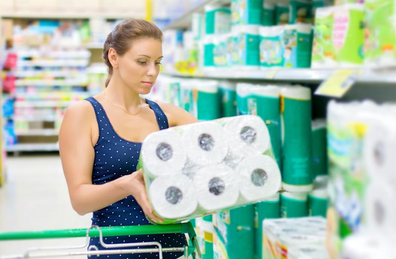 woman handles toilet paper in the supermarket as COVID-19 sells out the item
