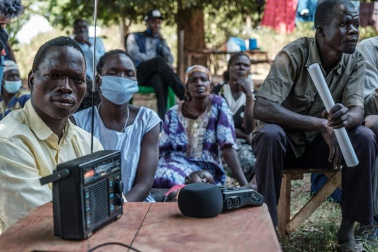 Mohammed Olanyia, left, who lost his family in a 2004 massacre, listens to the ICC verdict on Ongwen from Uganda