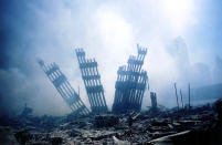 <p>The rubble of the World Trade Center smoulders. (Getty)</p>