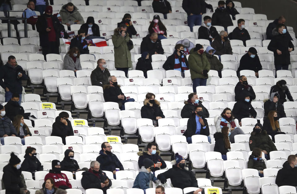 Fans are socially distanced as they wait for kick off ahead of the English Premier League soccer match between West Ham United and Manchester United at the London stadium in London, England, Saturday, Dec. 5, 2020. (Julian Finney/Pool Via AP)