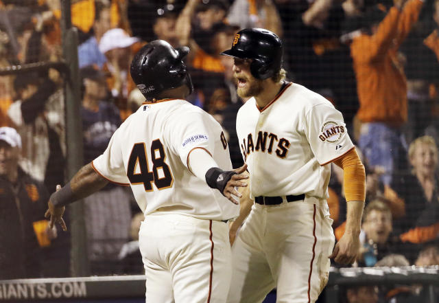 San Francisco Giants' Pablo Sandoval (48) and Hunter Pence celebrate after scoring on a double by Juan Perez during the eighth inning of Game 5 of baseball's World Series against the Kansas City Royals Sunday, Oct. 26, 2014, in San Francisco. (AP Photo/David J. Phillip)
