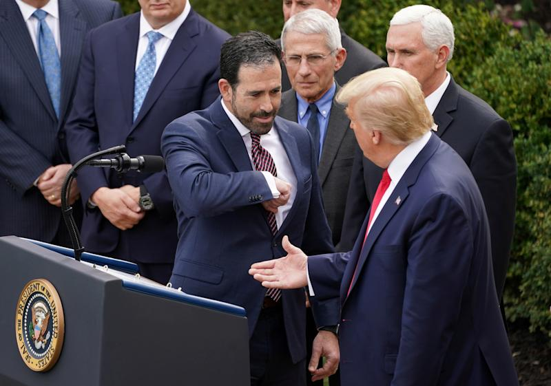 Bruce Greenstein, Executive Vice President and Chief Strategy and Innovation Officer of the LHC Group offers President Donald Trump an elbow bump in place of a handshake for safety as Dr Anthony Fauci and Vice President Mike Pence look on after the president declared the coronavirus pandemic a national emergency at a news conference in the Rose Garden of the White House in Washington, U.S., March 13, 2020. (Kevin Lamarque/Reuters)