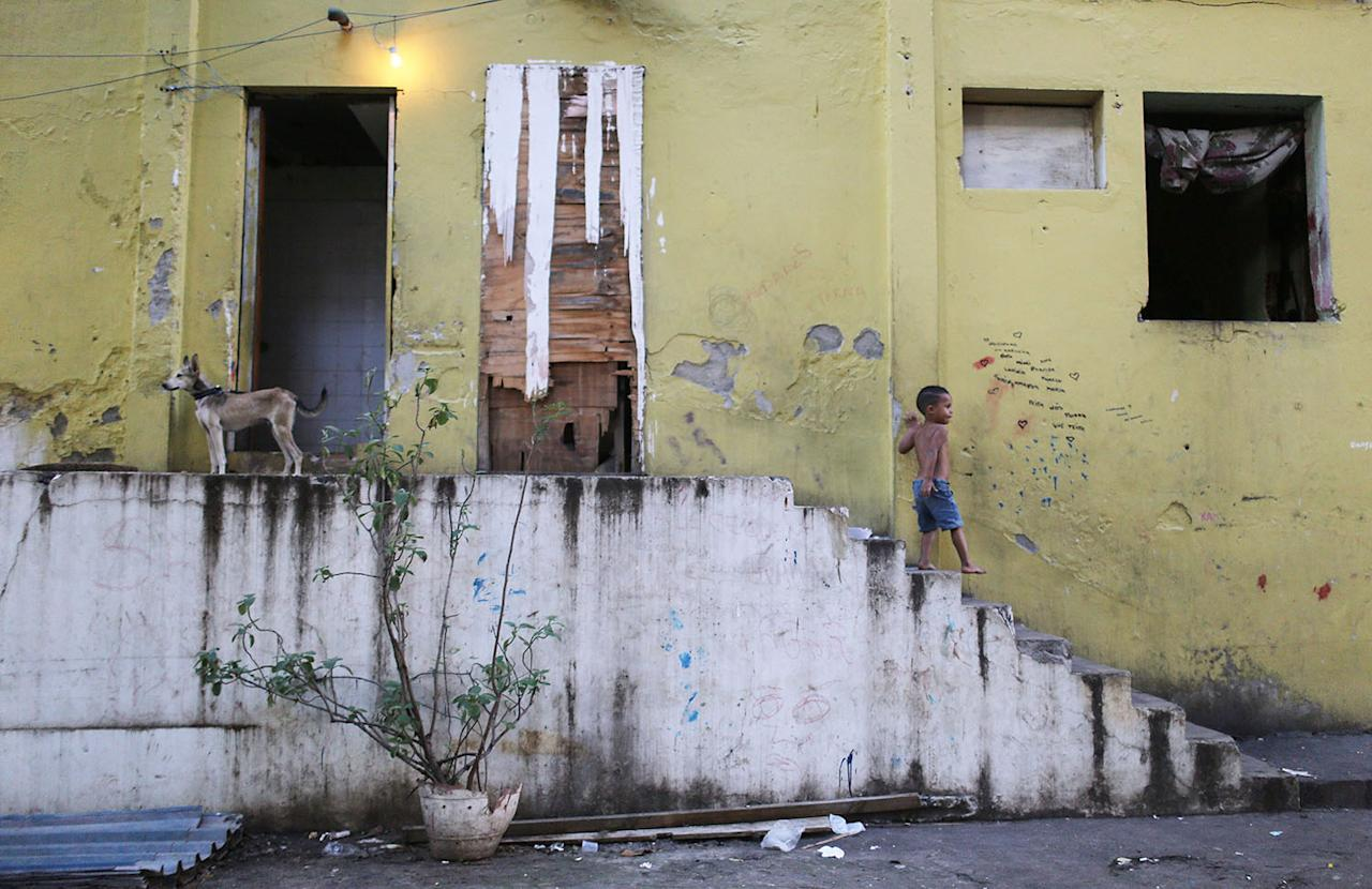 <p>A boy walks down the stairs in a set of occupied buildings in the Mangueira favela, May 4, 2017, in Rio de Janeiro. (Photo: Mario Tama/Getty Images) </p>