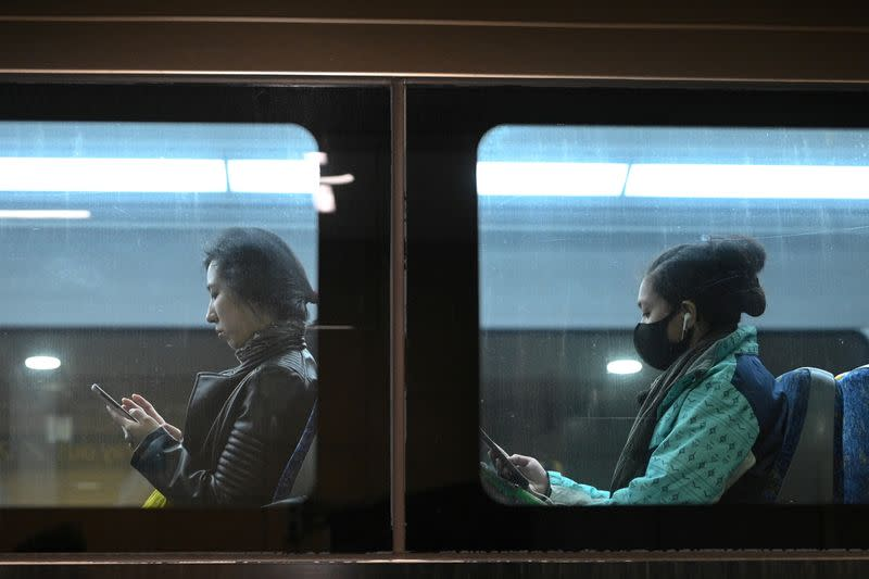FILE PHOTO: Commuters ride a train in Sydney