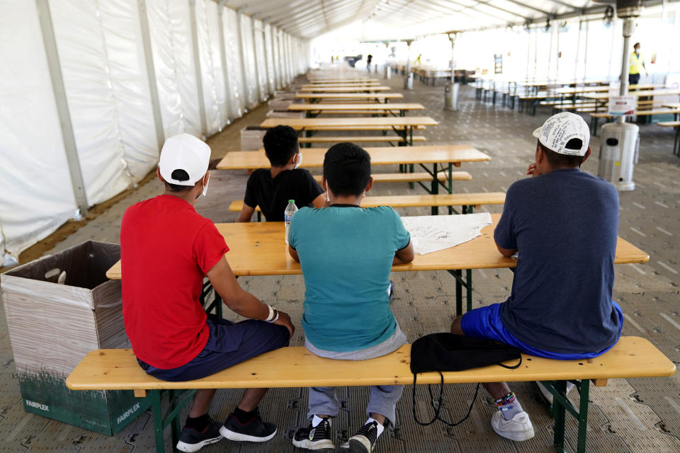 Children sit inside a dining tent at an emergency shelter for migrant children Friday, July 2, 2021, in Pomona, Calif. (AP Photo/Marcio Jose Sanchez, Pool)