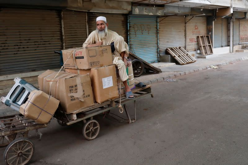 A labourer sits with supplies outside a closed market during a contrywide strike in Karachi,