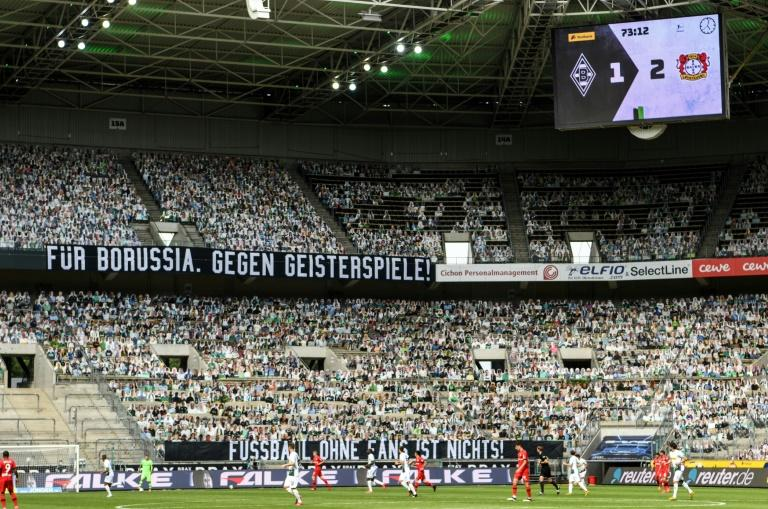 """Cardboard cut-outs of fans and a banner reading """"For Borussia, against matches behind locked doors"""" during Saturday's 3-1 defeat at home to Bayer Leverkusen"""
