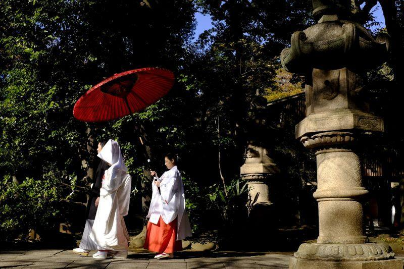 A couple walk in the garden of the Hikawa shrine during their traditional Shinto wedding ceremony in Tokyo