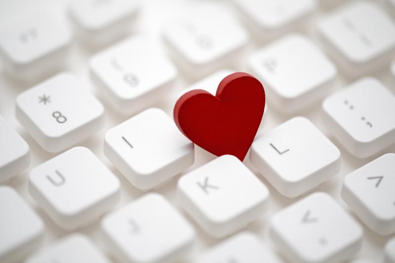 Small red heart on computer keyboard. Internet dating concept.
