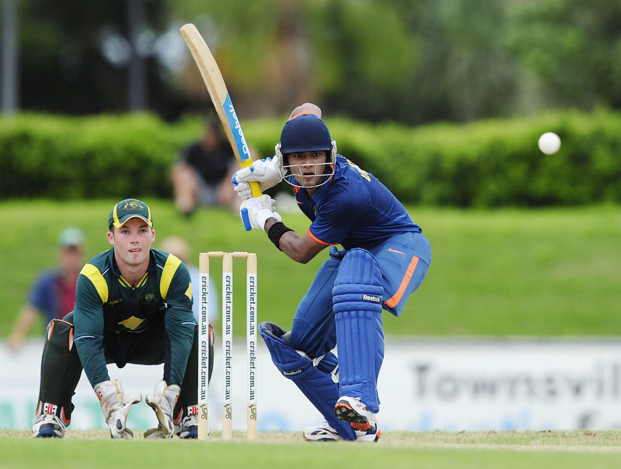 TOWNSVILLE, AUSTRALIA - APRIL 15:  Unmukt Chand of India bats in font of James Peirson of Australia during the match between Australia and India on day five of the U19 International Quad Series at Tony Ireland Stadium on April 15, 2012 in Townsville, Australia.  (Photo by Ian Hitchcock/Getty Images)