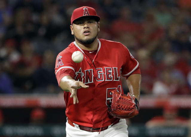 Los Angeles Angels starting pitcher Jaime Barria makes an underhand throw to first base to put out Texas Rangers' Elvis Andrus after a ground ball during the second inning of a baseball game Monday, Sept. 10, 2018, in Anaheim, Calif. (AP Photo/Marcio Jose Sanchez)