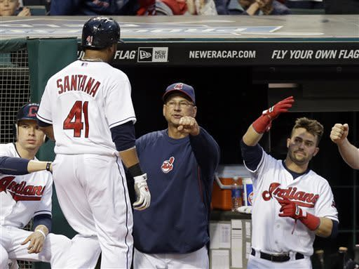 Cleveland Indians' Carlos Santana (41) is greeted by manager Terry Francona, center, and Nick Swisher after scoring on a sactifice fly by Yan Gomes in a baseball game against the Oakland Athletics, Tuesday, May 7, 2013, in Cleveland. (AP Photo/Mark Duncan)