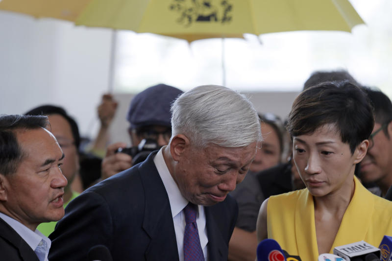 Occupy Central leader Chu Yiu-ming, center, cries as he speaks to media after sentencing at a court in Hong Kong, Wednesday, April 24, 2019. A court in Hong Kong handed down prison sentences of up to 16 months Wednesday to eight leaders of massive 2014 pro-democracy protests on charges of public nuisance offenses. (AP Photo/Kin Cheung)