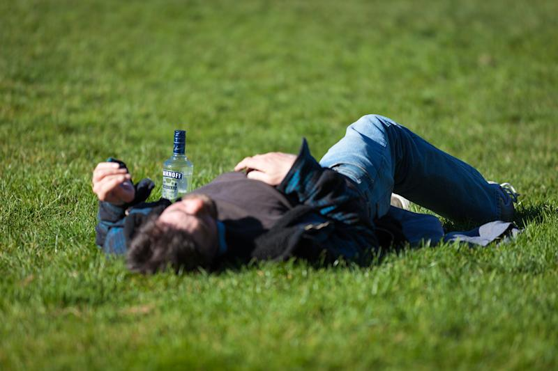 A man lies on the grass with a bottle of vodka next to him.
