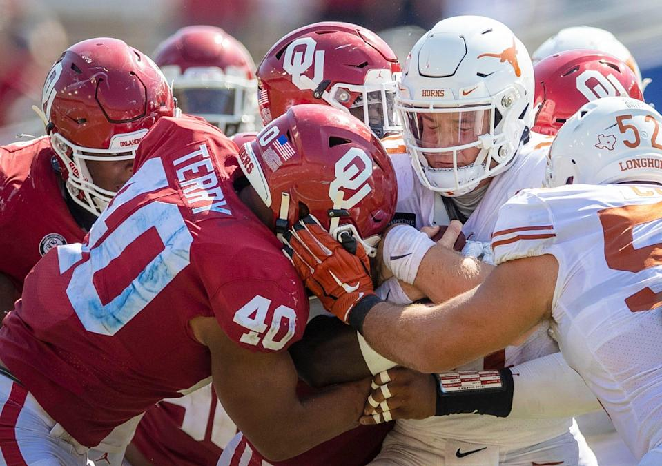 Texas Longhorns quarterback Sam Ehlinger (11) fights for yardage against Oklahoma Sooners defense in an NCAA college football game at the Cotton Bowl in Dallas.