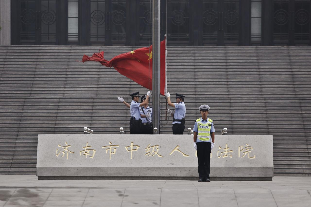 Policemen hoist a Chinese national flag in front of an entrance of the Jinan Intermediate People's Court where the trial of disgraced Chinese politician Bo Xilai will be held, in Jinan, Shandong province September 22, 2013. A Chinese court will announce its verdict on former top politician Bo on Sunday following his 5-day trial last month on charges of corruption and abuse of power. He could be handed a long jail term by the Communist Party-controlled court. REUTERS/Aly Song (CHINA - Tags: POLITICS CRIME LAW)