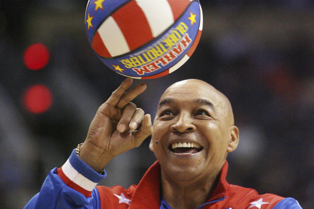 "FILE - In this Jan. 9, 2008, file photo, the Harlem Globetrotters' Fred ""Curly"" Neal performs during a timeout in the second quarter in an NBA basketball game between the Indiana Pacers and the Phoenix Suns in Phoenix. Neal, the dribbling wizard who entertained millions with the Harlem Globetrotters for parts of three decades, has died the Globetrotters announced Thursday, March 26, 2020. He was 77. Neal played for the Globetrotters from 1963-85, appearing in more than 6,000 games in 97 countries for the exhibition team known for its combination of comedy and athleticism. (AP Photo/Ross D. Franklin, File)"