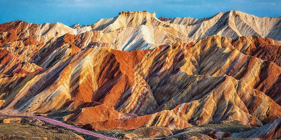 """<p>You've never seen anything quite like the <a href=""""https://www.tripadvisor.com/ShowUserReviews-g1850955-d1857482-r187748531-Zhangye_Danxia_Geopark-Linze_County_Gansu.html"""" rel=""""nofollow noopener"""" target=""""_blank"""" data-ylk=""""slk:Rainbow Mountains"""" class=""""link rapid-noclick-resp"""">Rainbow Mountains</a> within <a href=""""https://www.tripadvisor.com/Attraction_Review-g1850955-d1857482-Reviews-Zhangye_Danxia_Geopark-Linze_County_Gansu.html"""" rel=""""nofollow noopener"""" target=""""_blank"""" data-ylk=""""slk:Zhangye Danxia Landform Geological Park"""" class=""""link rapid-noclick-resp"""">Zhangye Danxia Landform Geological Park</a> in China's Gansu province. A combination of sandstone and minerals being pressed together over millennia and erosion have created vibrant streaks of reds, yellows, greens, and blues across the mountains to make a bizarre but fascinating Technicolor landscape. This UNESCO World Heritage Site is definitely one of the most beautiful places in the world. </p>"""