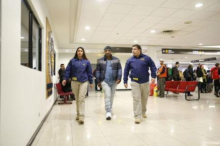 American boxer Mike Tyson (C) is escorted by members of the Investigative Police of Chile (PDI) at the Santiago International Airport in Santiago, Chile November 9, 2017. Courtesy of Policia de Investigaciones de Chile/Handout via REUTERS ATTENTION EDITORS - THIS IMAGE WAS PROVIDED BY A THIRD PARTY.