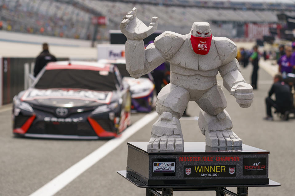 The trophy for a NASCAR Cup Series auto race is displayed with Martin Truex Jr. on the pole position before the race at Dover International Speedway, Sunday, May 16, 2021, in Dover, Del. (AP Photo/Chris Szagola)