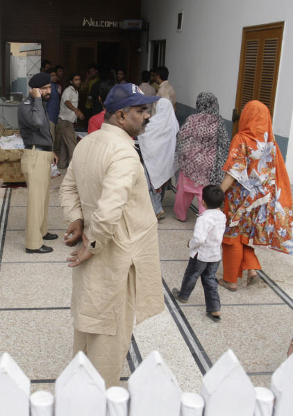 """People visit the house of shooting victims in Lahore, Pakistan on Monday, April 30, 2012. The widow and mother-in-law of one of two Pakistanis men shot and killed by a CIA contractor last year, have been murdered in Lahore, police said. It appears killings may have been related to the large amount of """"blood money"""" Zohra Haider received to pardon her husband's killer, Raymond Davis. (AP Photo/K.M. Chaudary)"""