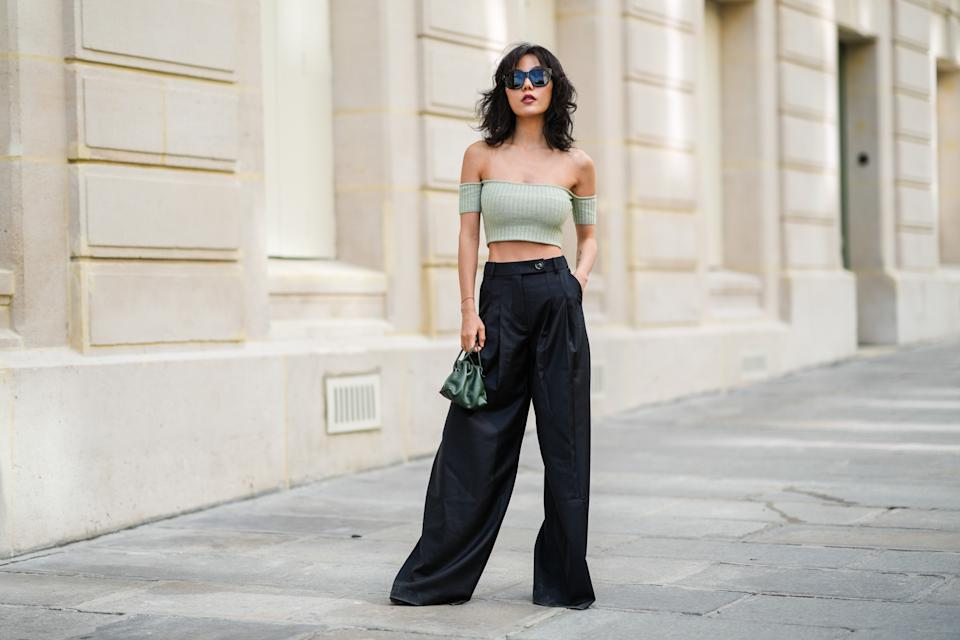 PARIS, FRANCE - AUGUST 22: Xiayan wears black large sunglasses, silver earrings, a pale green ribbed off-shoulders cropped t-shirt, black high waist flowing wide leg pants, a red bracelet, dark green shiny leather small handbag, black shiny leather block heels boots, on August 22, 2021 in Paris, France. (Photo by Edward Berthelot/Getty Images)