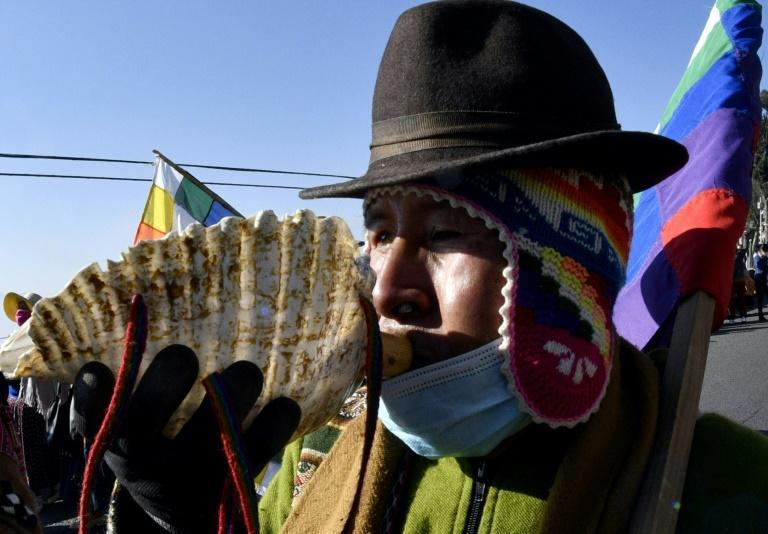 An Amauta, a priest of Bolivia's indigenous Aymara community, blows an instrument during an anti-government march