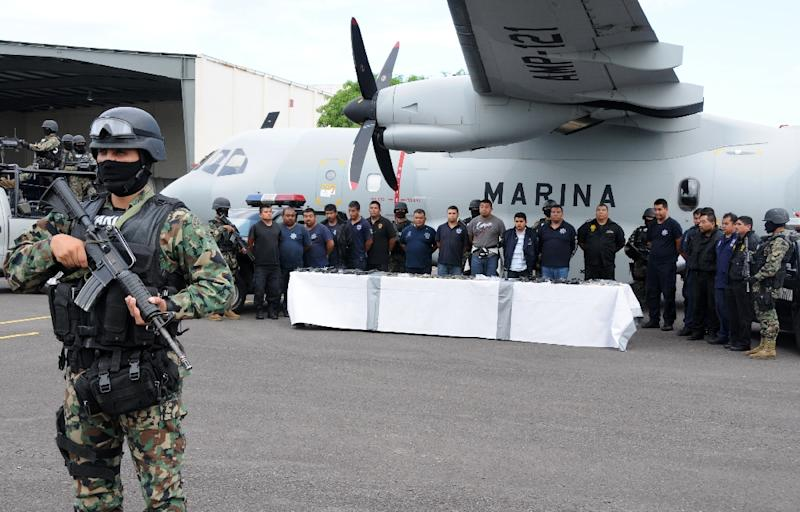 Mexican marines escort a group of alleged municipal policemen working for the Zeta cartel, five members of the same cartel and nine escaped inmates, in Veracruz, in 2011