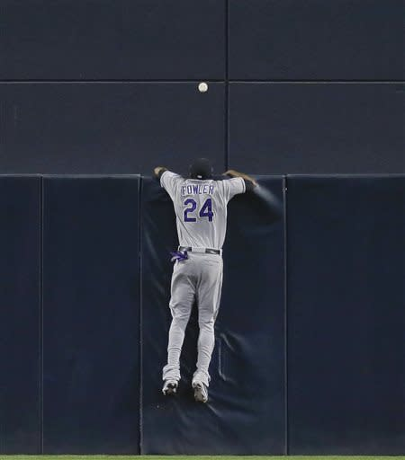 Colorado Rockies center fielder Dexter Fowler rest on the fence watching a two-run homer by San Diego Padres' Yonder Alonso during the first inning of a baseball game, Friday, April 12, 2013, in San Diego. (AP photo/Lenny Ignelzi)