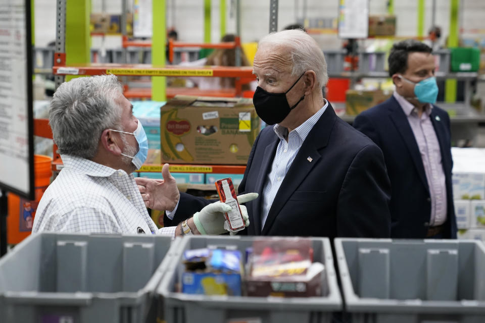 President Joe Biden talks with a volunteer at the Houston Food Bank, Friday, Feb. 26, 2021, in Houston. (AP Photo/Patrick Semansky)