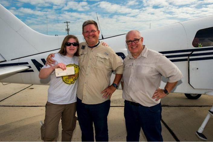 Erika Kelly, the president and founder of Operation Git-Meow, gives a check to pilots Stephen Merritt and Michael Plante to help them with the costs they incurred on their recent trip to Guantánamo Bay