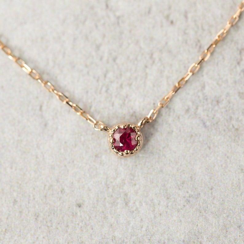 """<h2>July: Ruby</h2><br>When you wear ruby, you're channeling the three P's: passion, prosperity, and protection. """"For many years it was thought to make the wearer invincible, making it one of the most prized of all gems,"""" explains Montúfar. """"However powerful and pretty, it also helps the body go through all sorts of detoxifying processes.""""<br><br><strong>EnveroJewelry</strong> Ruby Necklace, $, available at <a href=""""https://www.etsy.com/listing/597991670/round-ruby-necklace-14k-rose-gold-ruby"""" rel=""""nofollow noopener"""" target=""""_blank"""" data-ylk=""""slk:Etsy"""" class=""""link rapid-noclick-resp"""">Etsy</a>"""