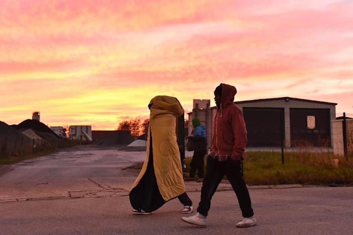 "Migrants walk at sunset near the ""Jungle"" migrant camp in Calais, northern France, on October 27, 2016 (AFP Photo/Philippe Huguen)"