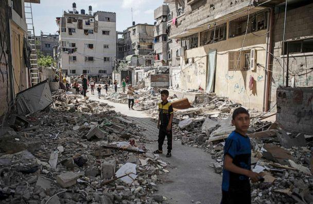 PHOTO: Palestinian children walk next to rubble from a house was that was hit by early morning Israeli airstrikes, in Gaza City, May 17, 2021. (Khalil Hamra/AP)