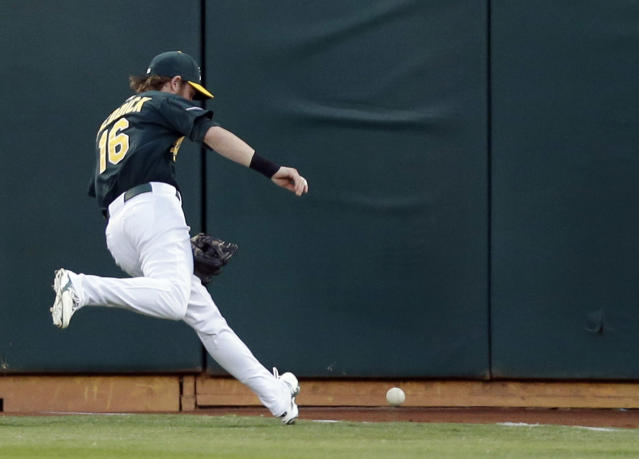 Oakland Athletics right fielder Josh Reddick goes after a double by Detroit Tigers' Austin Jackson in the first inning of Game 1 of the American League baseball division series in Oakland, Calif., Friday, Oct. 4, 2013. (AP Photo/Marcio Jose Sanchez)