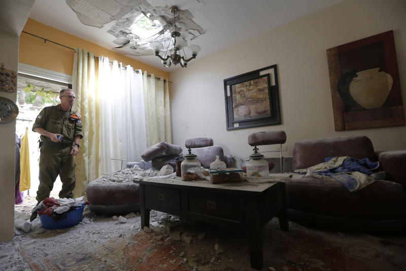 An Israeli soldier surveys the damage to a house after a rocket fired by Palestinian militants from Gaza Strip hit a community in southern Israel, Wednesday, Oct. 24, 2012. Rockets and mortars from Gaza have pummeled southern Israel, drawing Israeli airstrikes that killed a Palestinian militant. The Israeli military said 60 rockets and mortars were fired by early morning Wednesday, following a volley the night before and that Israeli aircraft struck Gaza three times. (AP Photo/ Tsafrir Abayov)
