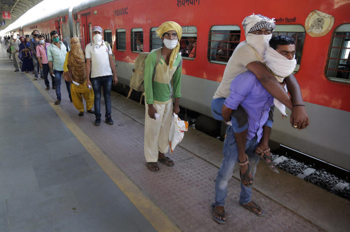 Hira Ali carries his physically disabled brother, Muslim Ali, on his back as they wait to board a special train to return to Agra in Uttar Pradesh state, during a nationwide lockdown to curb the spread of new coronavirus, at a railway station in Ahmedabad, in the western Indian state of Gujarat, on Saturday, May 2, 2020. Tens of thousands of impoverished migrant workers are on the move across India, walking on highways and railway tracks or riding trucks, buses and crowded trains in blazing heat. They say they have been forced to leave cities and towns where they had toiled for years building homes and roads after they were abandoned by their employers due to a lockdown to stop the virus from spreading. (AP Photo/Ajit Solanki)