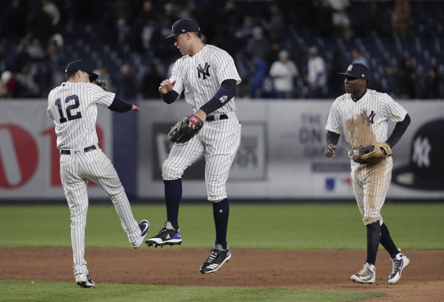 New York Yankees' Tyler Wade (12), Aaron Judge, center, and Didi Gregorius celebrate after the Yankees defeated the Toronto Blue Jays 4-3 in a baseball game Thursday, April 19, 2018, in New York. (AP Photo/Julie Jacobson)