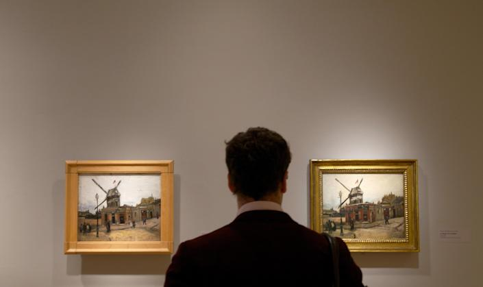 """In this Oct. 8, 2013 photo, a visitor looks at Vincent van Gogh's """"Le Moulin de la Galette,"""" on display at The Phillips Collection in Washington. In the midst of the shutdown of federally funded museums, the private Phillips Collection is launching the first major exhibition of Vincent van Gogh's artwork in Washington in 15 years. (AP Photo/Molly Riley)"""