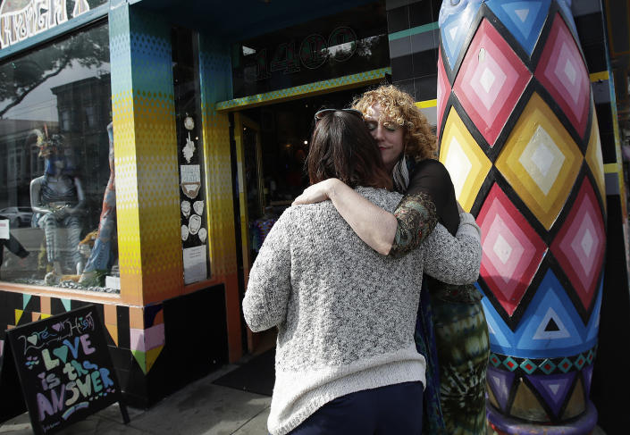 In this Oct. 1, 2018 photo, Sunshine Powers, owner of the store Love on Haight, right, hugs Christin Evans, owner of The Booksmith, outside of Powers' store in San Francisco. A measure on San Francisco's Nov. 6 ballot would levy an extra tax on hundreds of the city's wealthiest companies to raise $300 million for homelessness and mental health services. It's the latest battle between big business and social services advocates who say that companies such as Amazon, Google and Salesforce can afford to help solve severe inequities caused by business success. (AP Photo/Jeff Chiu)