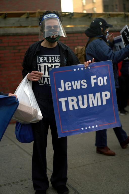 A man holds a Jews for Trump sign as members of the Sephardic Jewish Community in Brooklyn, New York protest the closing of businesses and a new lockdown in their neighborhood on October 8, 2020