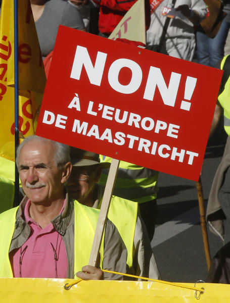 """A demonstrator holds a placard which reads,""""No to the Europe of Maastrich"""" to protest against the austerity measures announced by the French government, in Paris, Sunday, Sept 30, 2012. (AP Photo/Michel Euler)"""