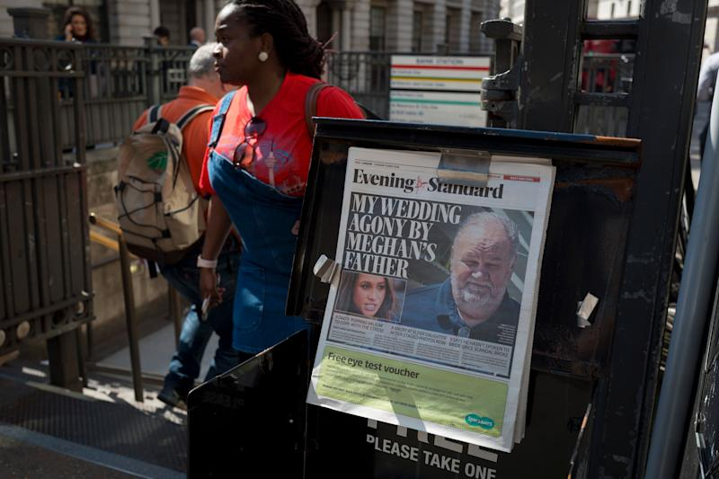 A newspaper dispenser with Meghan and her father on the front page