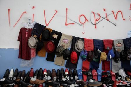 Clothes on sale are seen hung at a street stand next to graffiti, that was painted in the past, supporting Interim Prime Minister Jean-Michel Lapin, who has resigned today, along a street of Port-au-Prince