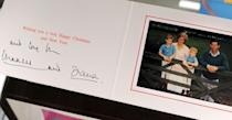<p>The family pose for a Christmas photo with the young boys wearing matching blue polo shirts. The card is signed by Charles and Diana. </p>