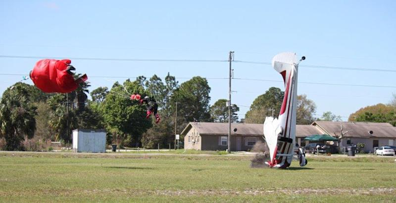 This photo released by the Polk County Sheriff's Office shows a plane nose-diving into the ground after getting tangled with a parachutist, left, Saturday March 8, 2014, at the South Lakeland Airport in Mulberry, Fla. Both the pilot and jumper hospitalized with minor injuries. (AP Photo/Polk County Sheriff's Office, Tim Telford) MANDATORY CREDIT