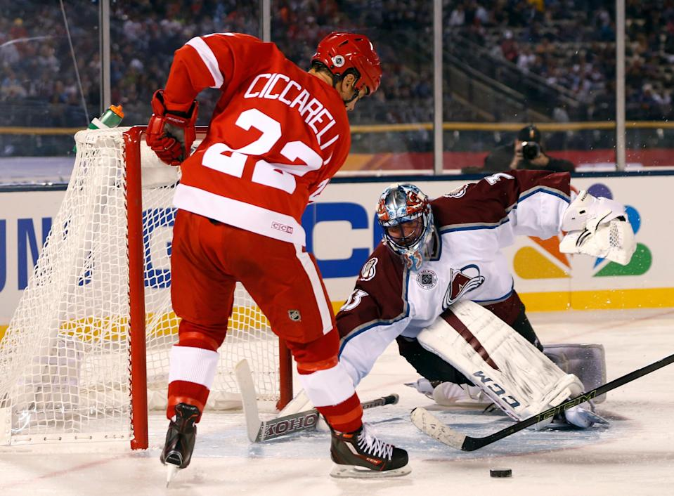 Red Wings right wing Dino Ciccarelli, left, takes a shot against Avalanche goalie Patrick Roy during the second period of the Wings' 5-2 loss in the alumni game Friday at Coors Field.