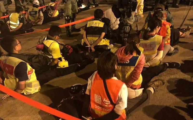 A viral photograph of medical staff sitting on the ground, their hands bound behind their backs with zip-cords, caused outrage in Hong Kong.