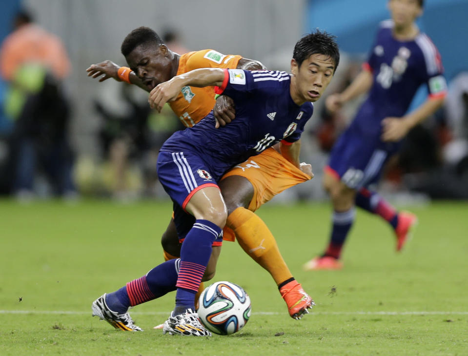 Japan's Shinji Kagawa, front, battles for the ball with Ivory Coast's Serge Aurier during the group C World Cup soccer match between Ivory Coast and Japan at the Arena Pernambuco in Recife, Brazil, Saturday, June 14, 2014. (AP Photo/Ricardo Mazalan)
